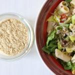 Ein Glas mit veganem Parmesan und neben eine Salatschüssel