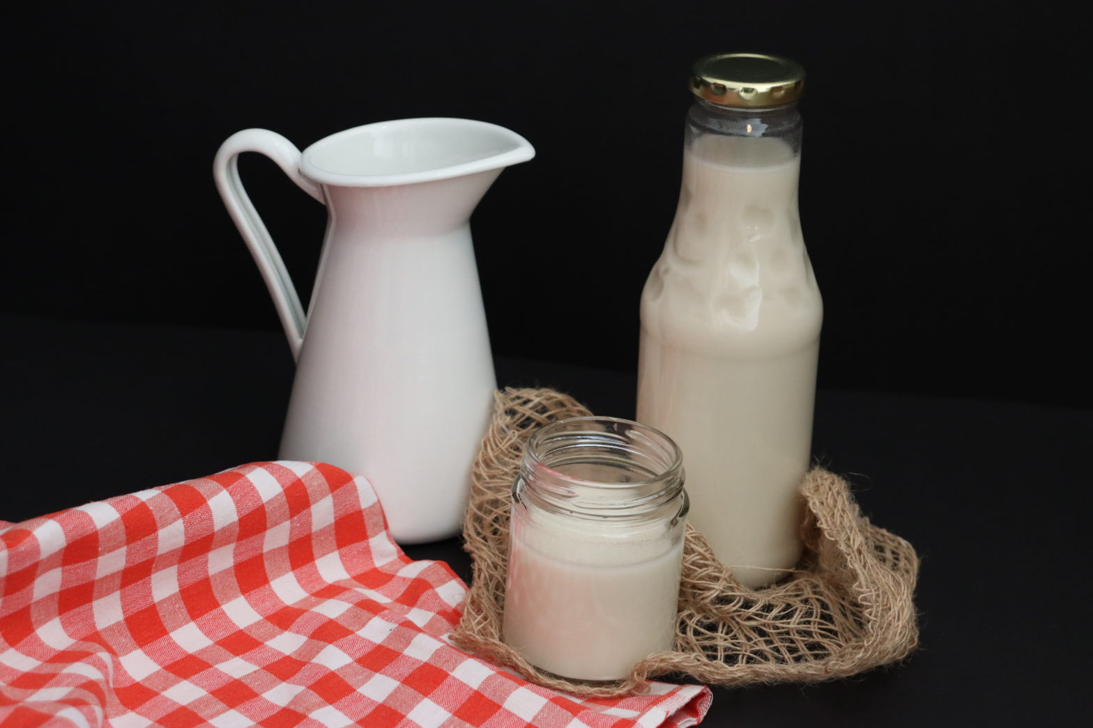 kleines Glas und Flasche mit Hafermilch