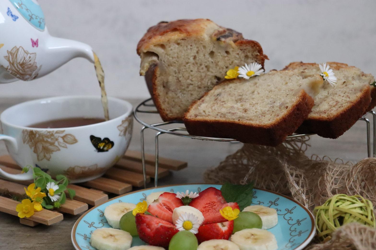 veganes Bananenbrot mit einer Tasse Tee und Teller voller Obst