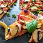 vegane Pizzascheiben belegt mit Zucchini, Zwiebeln, Tomaten, Paprika und frische Basilikumblätter