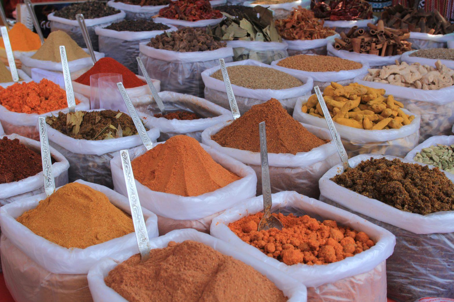 Säcke voll mit bunte pulverisierte Gewürze auf einem Markt