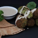 Bunch of backed Falafel balls decorated with fresh cilantro and parsley leafs, tahini sauce and arabic flat bread